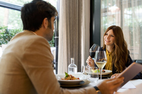 Smiling woman with glass of red wine looking at man in a restaurant - VABF01655