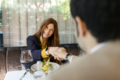Smiling woman shaking hands with man and in a restaurant - VABF01658