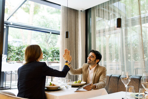Happy man and woman with a tablet in a restaurant high fiving - VABF01661