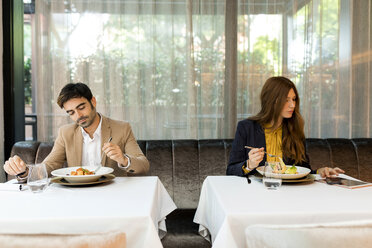 Man eating and woman using tablet in a restaurant - VABF01664