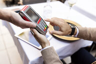 Man entering pin into card reader in a restaurant - VABF01676