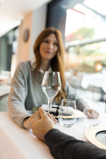 Woman holding hands with man in a restaurant - VABF01682