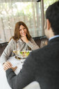 Smiling woman holding hands with man in a restaurant - VABF01688