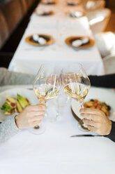 Close-up of couple clinking wine glasses in a restaurant - VABF01691