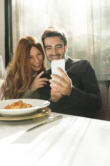 Happy couple looking at cell phone in a restaurant - VABF01697