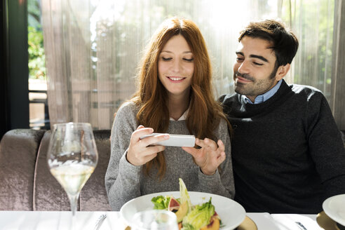 Smiling couple using cell phone in a restaurant - VABF01700