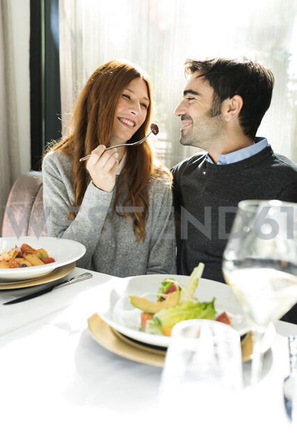 Smiling woman letting man taste the food in a restaurant - VABF01703