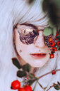 Close-up fashion portrait of young woman with red berries - INGF06956