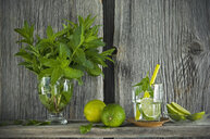 Homemade mint lemonade with lime on rustic wooden board - ASF06251