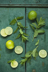 Mint and limes on rustic wooden background - ASF06254