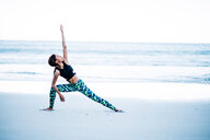African American woman doing yoga exercises on the beach by sea - INGF07012