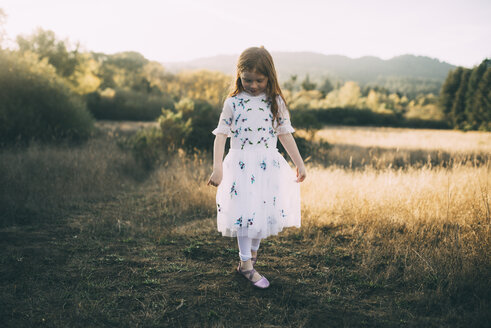 Full length of girl wearing white dress while playing at park - CAVF54156