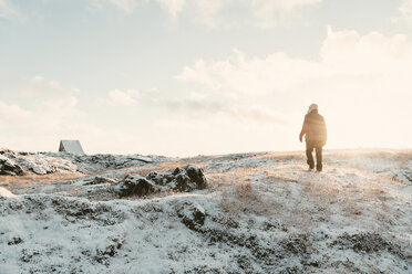 Hiker walking on snowy field during sunny day - CAVF54171