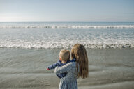 Rear view of girl carrying sister at beach - CAVF54204