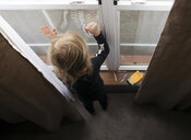 High angle view of girl drawing on window with crayons at home - CAVF54270