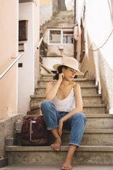 Thoughtful tourist wearing hat while sitting by backpack on steps in city - CAVF54282