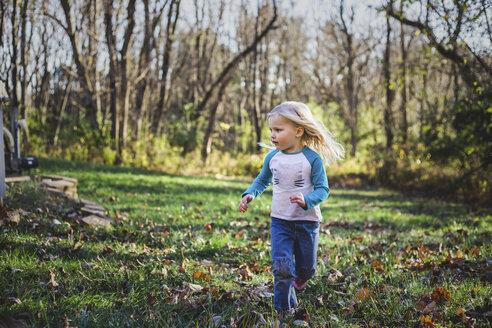 Girl running on grassy field at park during autumn - CAVF54300