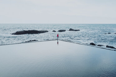 Mid distance view of woman standing amidst swimming pool and sea against clear sky - CAVF54333