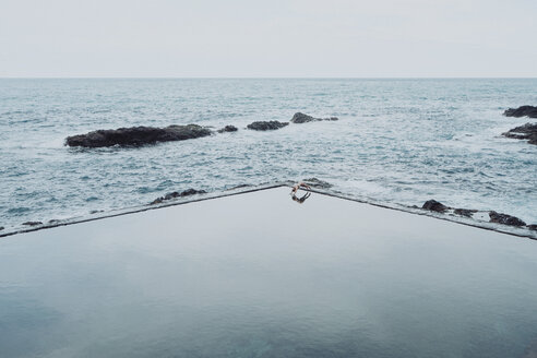 High angle view of woman diving into swimming pool against sea and clear sky - CAVF54336