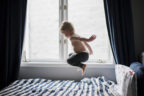 Shirtless boy jumping on bed by window at home - CAVF54351