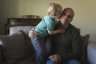 Son kissing father while standing on sofa at home - CAVF54375