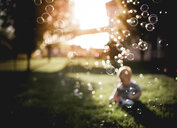 Baby boy playing at back yard with bubbles flying in foreground - CAVF54381