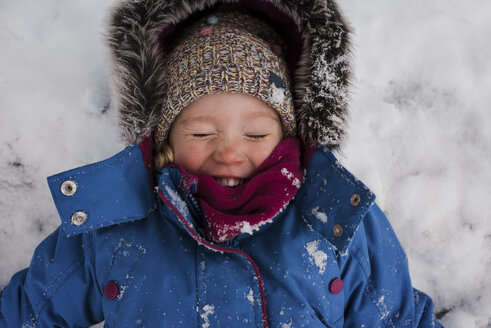 High angle view of smiling girl with eyes closed lying on snow covered field - CAVF54399