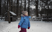 Girl walking on snow covered field in forest - CAVF54402