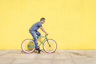 Side view of man riding bicycle against yellow wall at sidewalk in city - CAVF54408