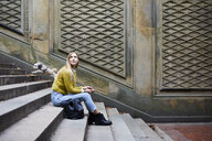 Side view of woman looking away while sitting on steps at park - CAVF54471