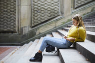 Full length side view of woman using smart phone while sitting on steps at park - CAVF54474