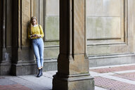 Full length of woman using mobile phone while standing by wall - CAVF54480