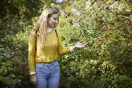 Smiling woman looking at plants while standing on field - CAVF54483