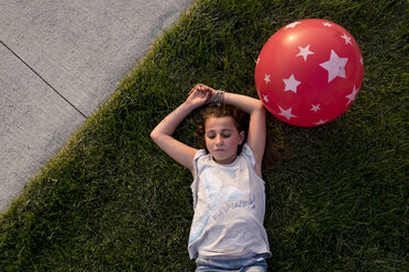 Overhead view of girl lying on grass with balloon at backyard - CAVF54516