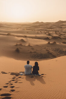 Rear view of friends sitting on sand at Sahara Desert against sky during sunset - CAVF54519
