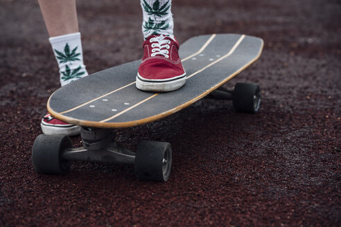 Woman's legs in socks and sneakers standing on carver skateboard - VPIF00973