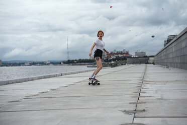 Young woman riding carver skateboard at the riverside - VPIF00988