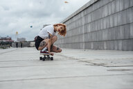 Young woman crouching on carver skateboard on a promenade - VPIF00991