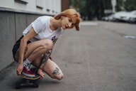 Young woman crouching on carver skateboard on a street - VPIF01003
