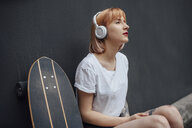 Young woman with skateboard and headphones listening to music - VPIF01012