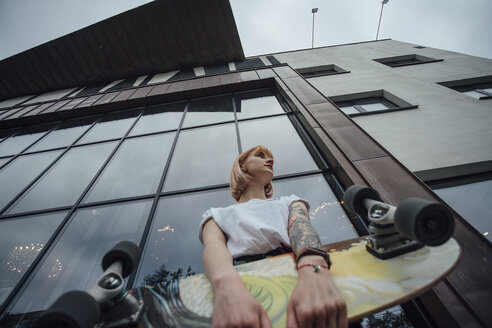 Young woman holding carver skateboard outside a building - VPIF01024