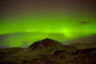 Scenic view of a snow covered mountain under a green sky at night - INGF07191