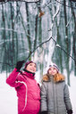 Mother and daughter during a walk in the snowy forest - INGF07317