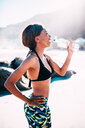 Fit young female athlete drinking water after workout on beach - INGF07428