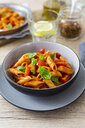 Penne with tomato and basil in bowl - GIOF04818