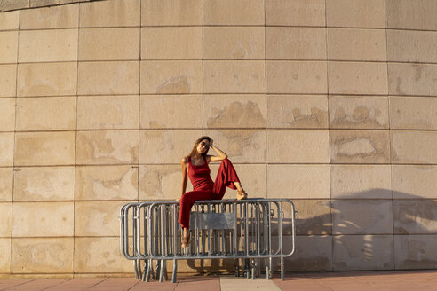 Spain, Barcelona, Montjuic, young woman wearing red jumpsuit sitting on barriers - AFVF01954