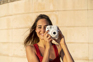 Portrait of smiling young woman taking instant photo outdoors - AFVF01957