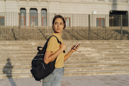 Young woman with cell phone and backpack on the go - AFVF01963