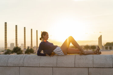 Spain, Barcelona, Montjuic, young woman lying on a wall at sunset - AFVF01966