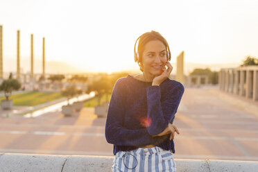 Spain, Barcelona, Montjuic, smiling young woman listening to music with headphones at sunset - AFVF01969